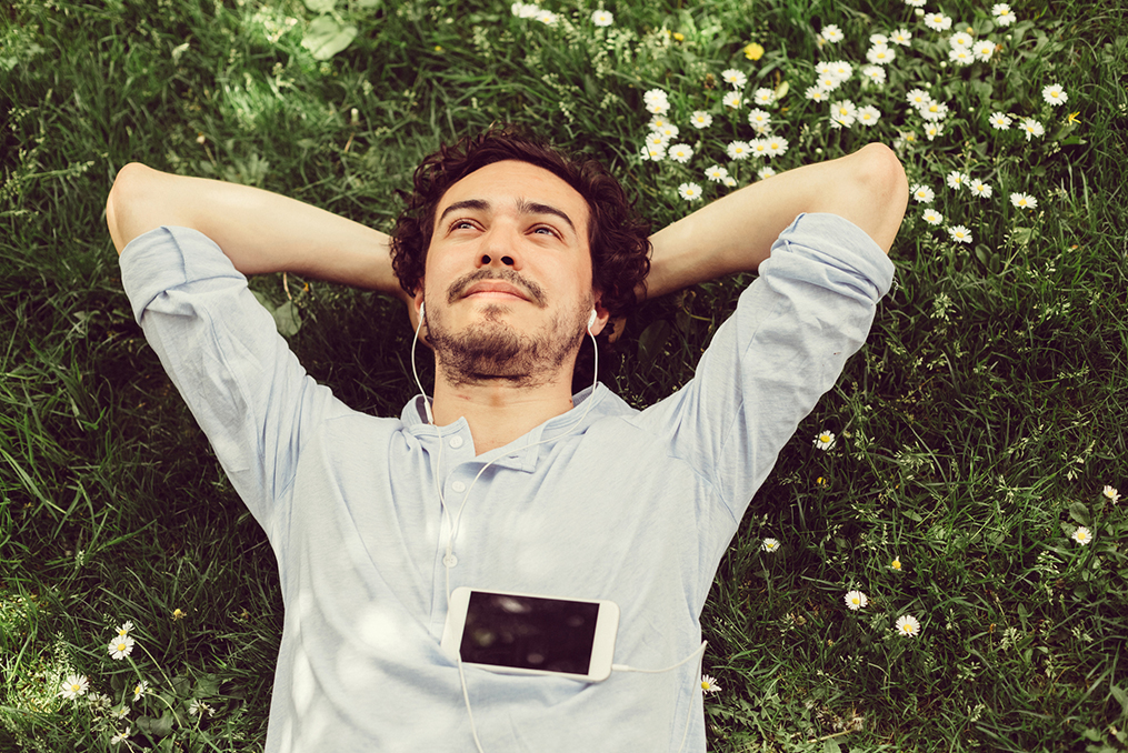 man laying in the grass with his hands behind his back listening to music