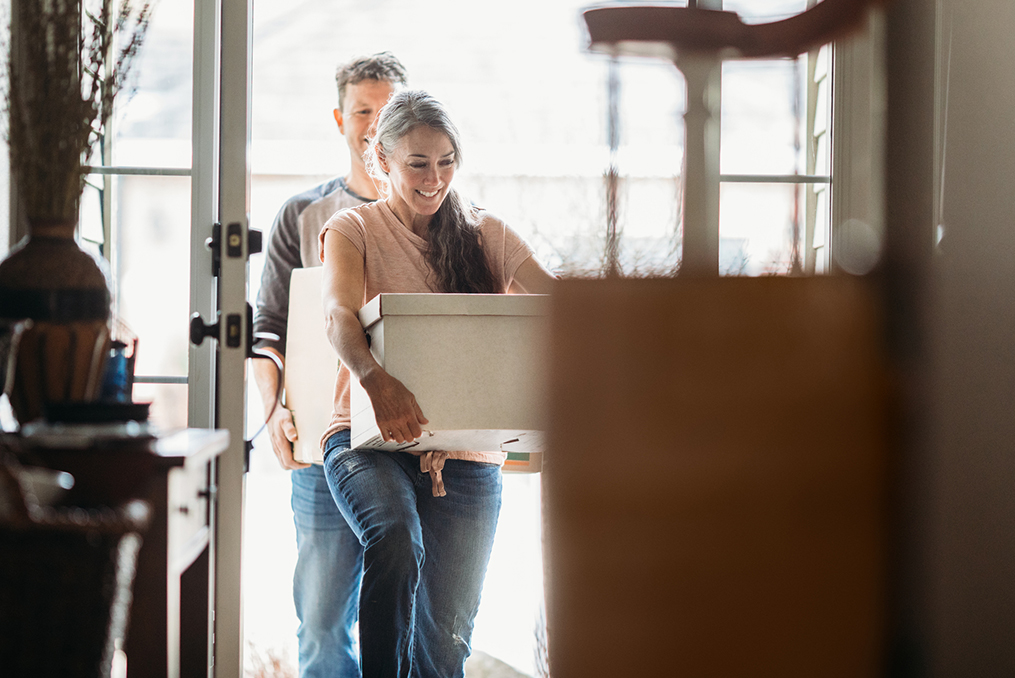 mature couple moving boxes through the back door of their home