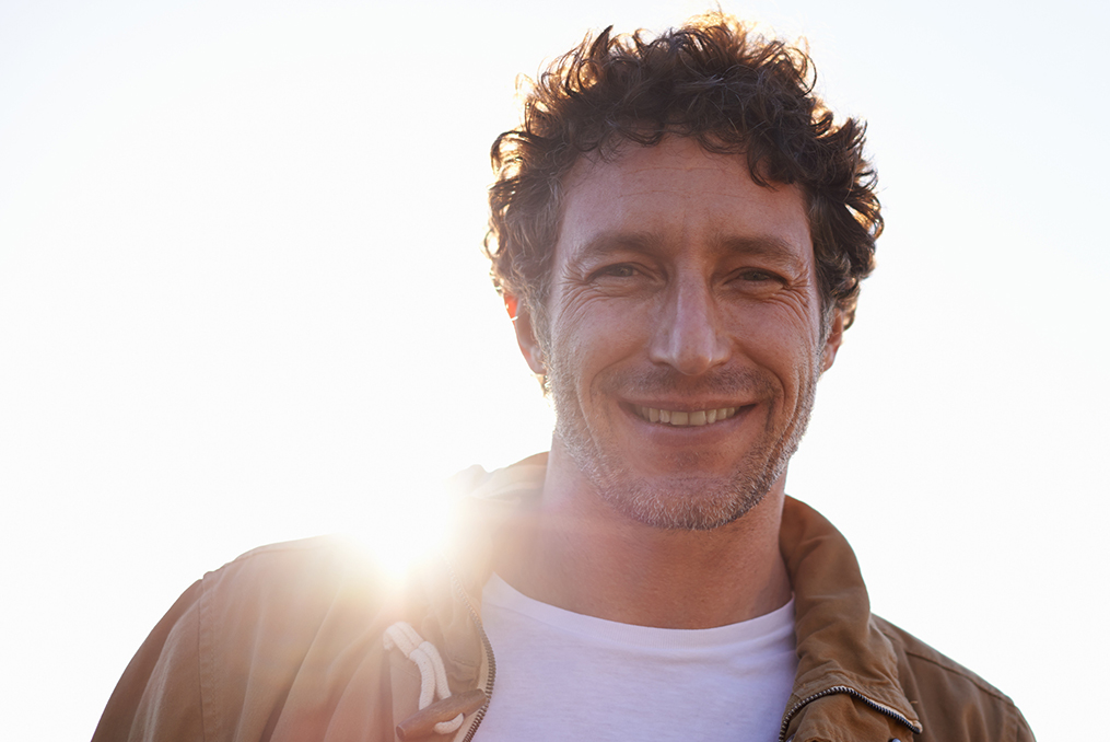 middle age man with facial hair smiling at the camera with the sun shining behind him