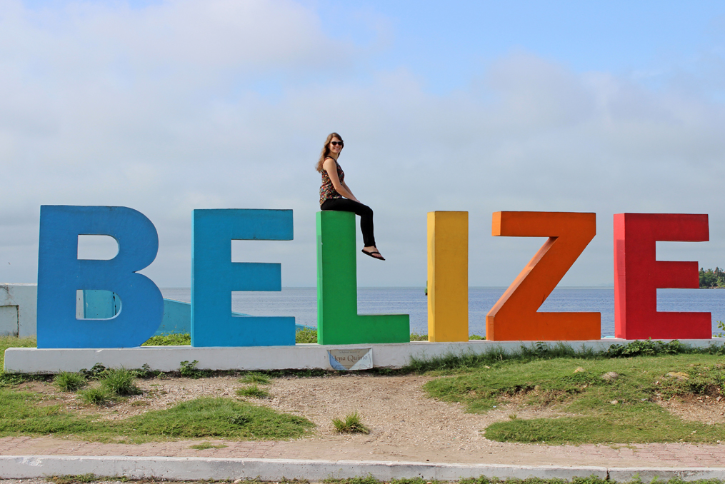 monica almroth sitting on the Belize sign at the beach