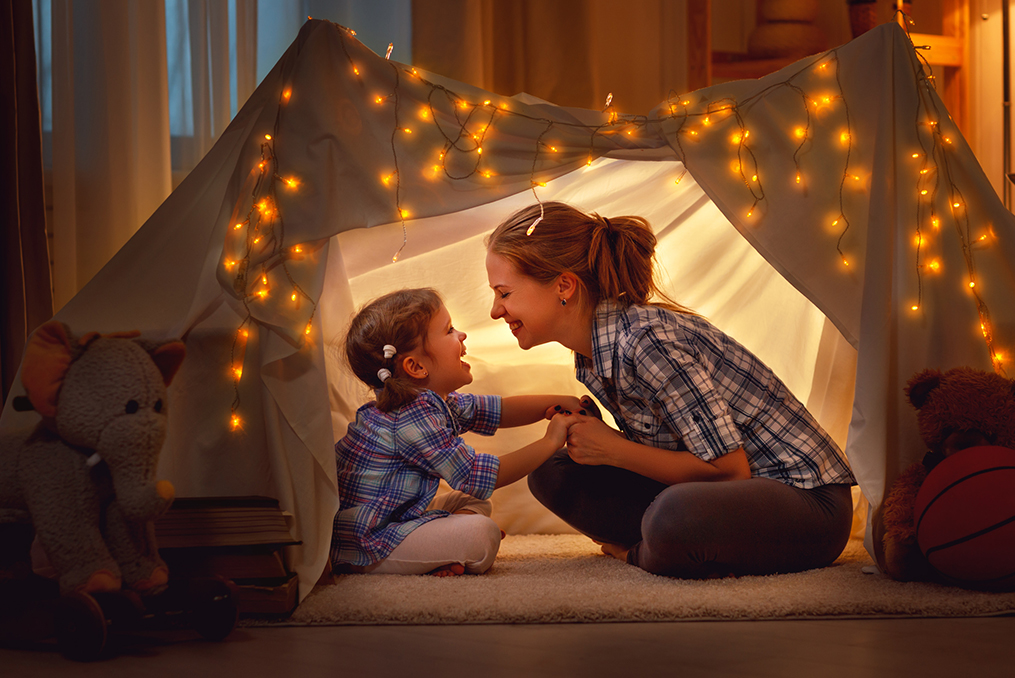 mother and daughter hanging out in a fort they built in their living room