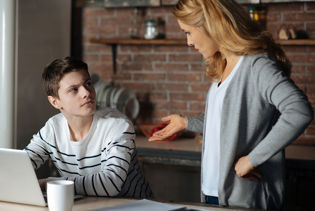 mother talking to her skeptical teenage son while he works on his laptop