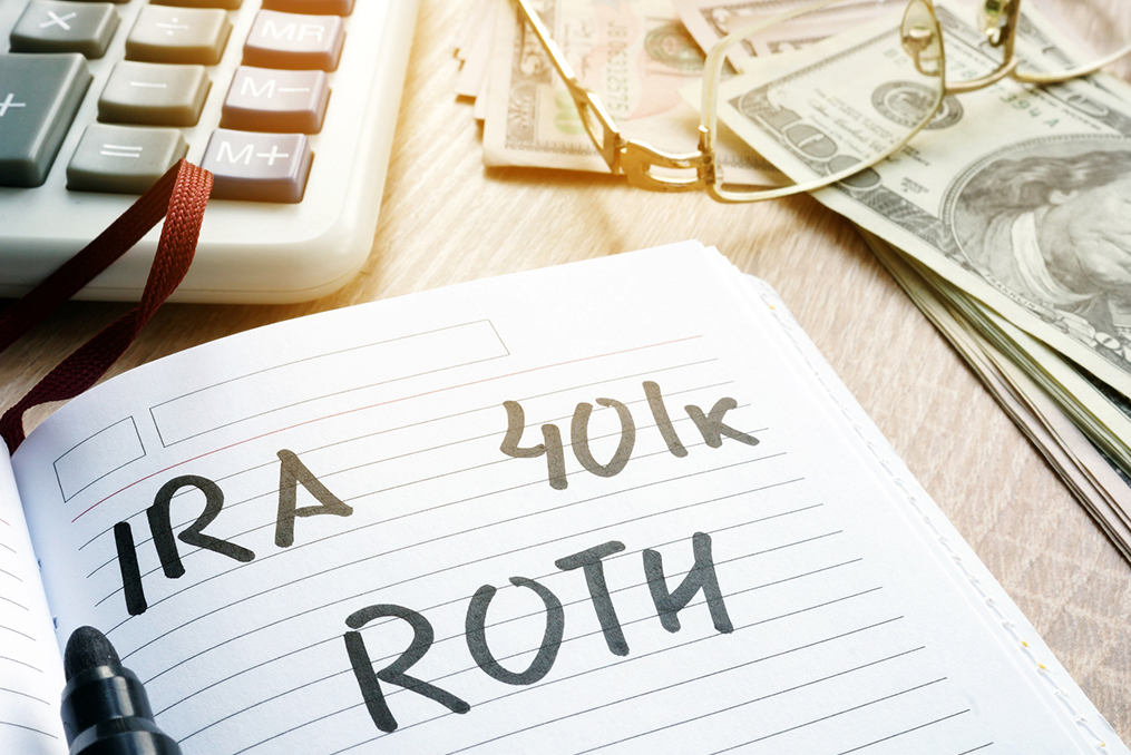 notepad with IRA 401k and ROTH written on it with money and calculator on the table nearby