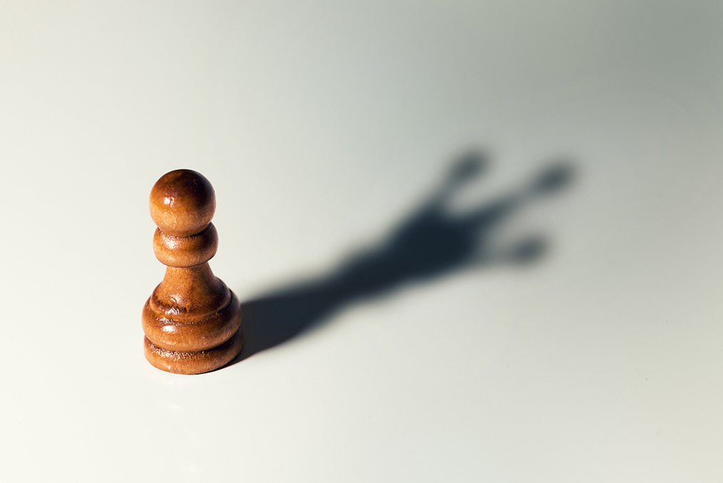 pawn casting the shadow of a king chess piece