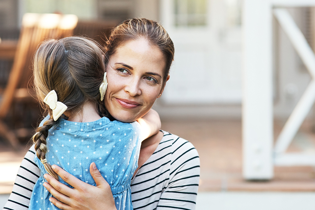 single mom giving her daughter a hug with a thoughtful look on her face