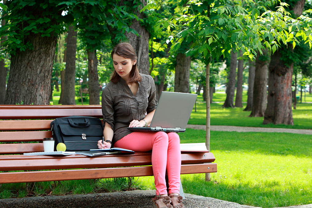 sitting on a park bench organizing finances during her lunch break