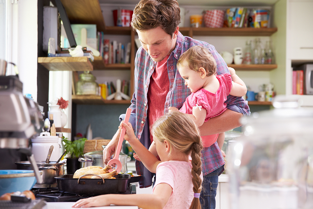 stay at home dad preparing dinner with his two young daughters