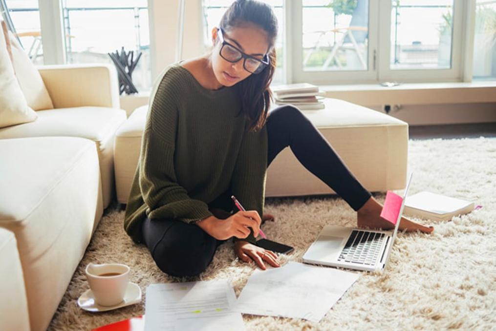 teenage girl sitting on the floor studying finances