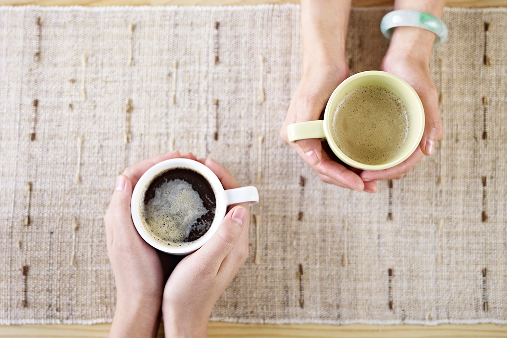two sets of hands holding separate cups of coffee