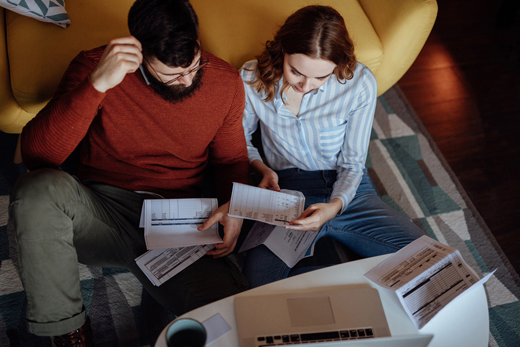 woman and man concentrating on financial documents sitting on the floor in front of their couch