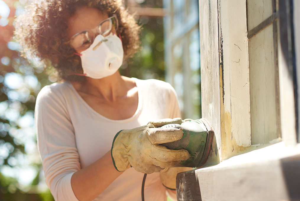 woman sanding a window frame on the outside of her new home making some home improvements