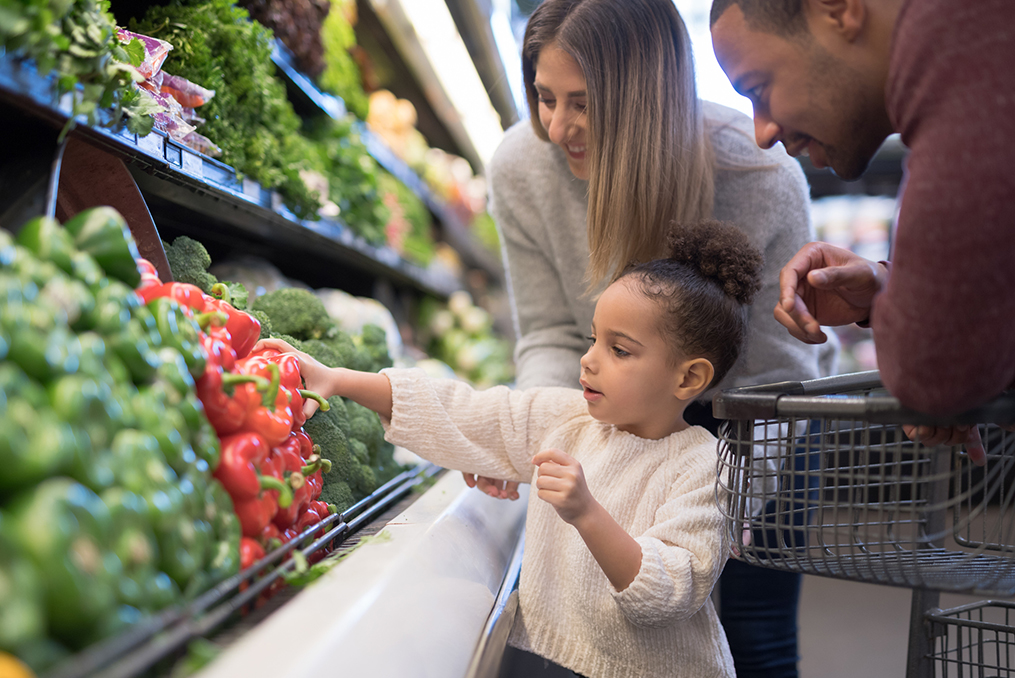 young child helping her parents pick out vegetables at the grocery store