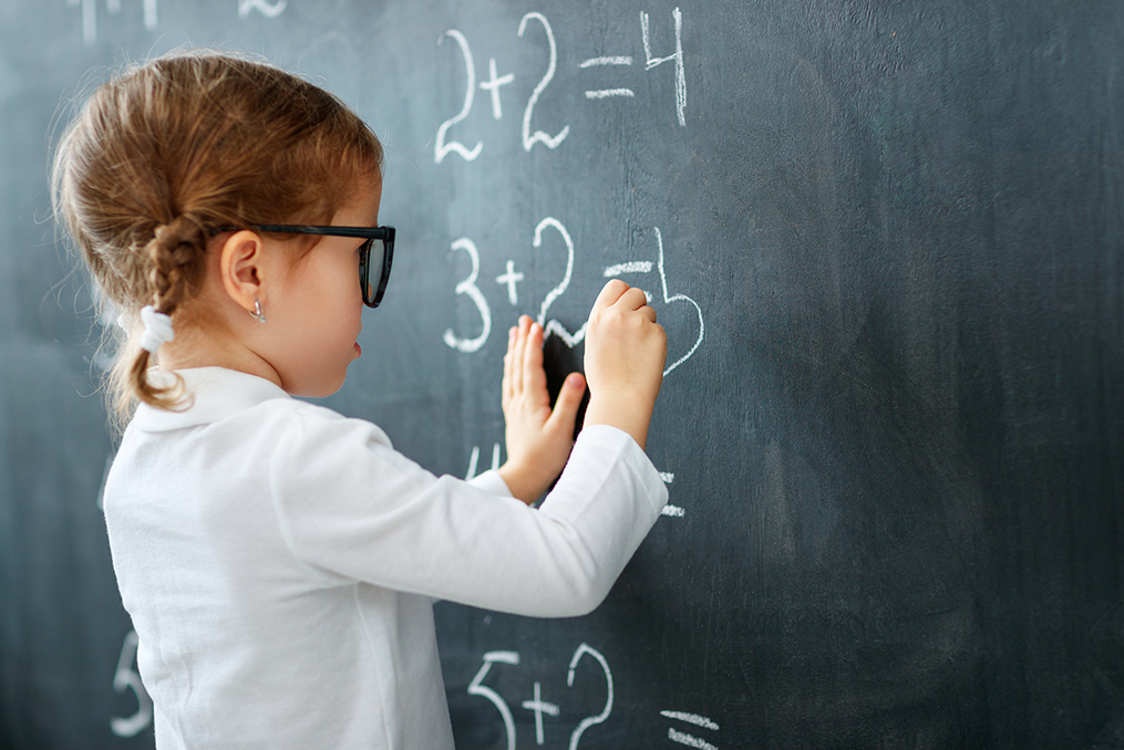 young girl writing math equations on a chalk board