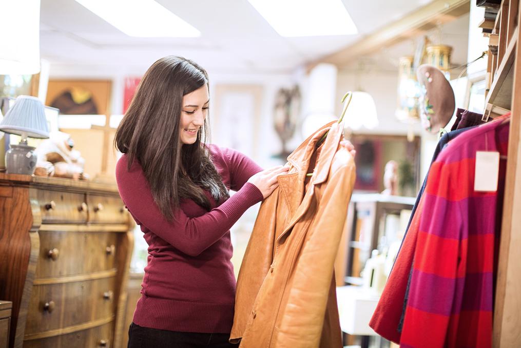 young woman looking at clothing at a thrift shop