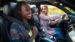 Young women in car, passenger holding seatbelt.