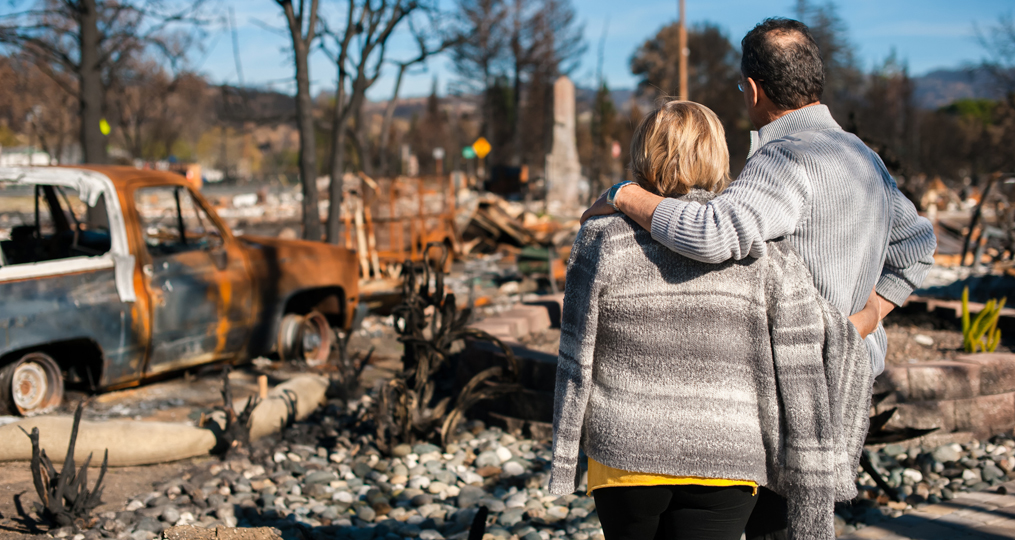 Emergency preparedness and disaster planning in the pacific northwest_family looking at aftermath of house fire_1015x540