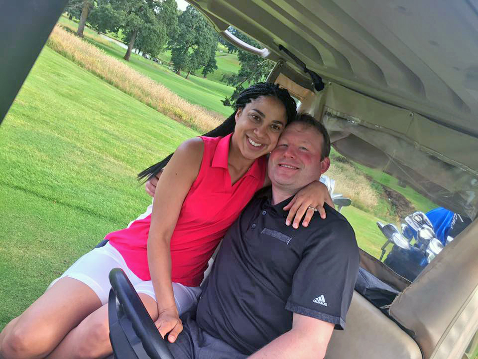 Guy and his wife sitting on a golf cart enjoying the sunshine and the game