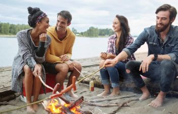 two couples roasting hot dogs over camp fire