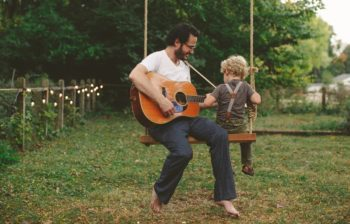 man with guitar sharing swing with child