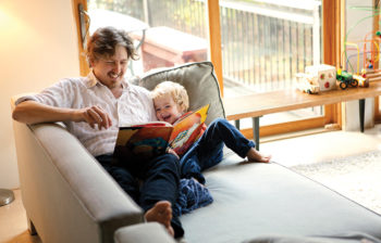 man reading book to happy child on couch