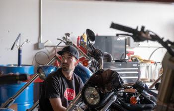 man in baseball cap working on motorcycle in garage