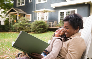 mother and child reading a book in the yard
