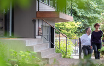 man and woman walking up steps to home