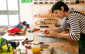 craftswoman in shoe workshop working