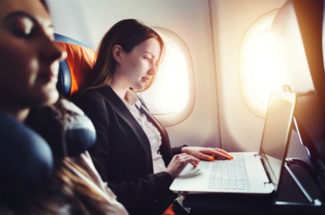 Woman sitting on a plane using her laptop.