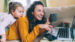Young woman and her daughter sitting on the couch looking at her laptop