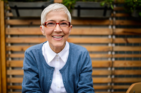mature senior woman with trendy glasses and sweater smiling