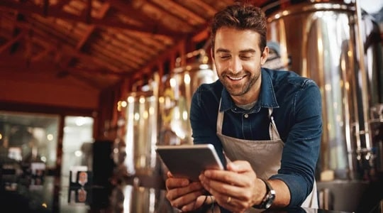 small business owner looking at a tablet at his brewery