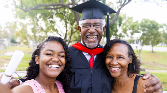 older man pursuing higher education with the support of his family
