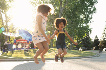 two girls jumping in the air at a neighborhood bar-b-que
